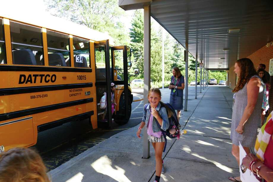 It's a happy day as children get off the school bus at West School in New Canaan, August 29, 2019. Photo: Grace Duffield / Hearst Connecticut Media
