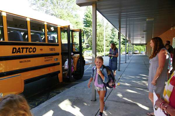 It's a happy day as children get off the school bus at West School in New Canaan, August 29, 2019.