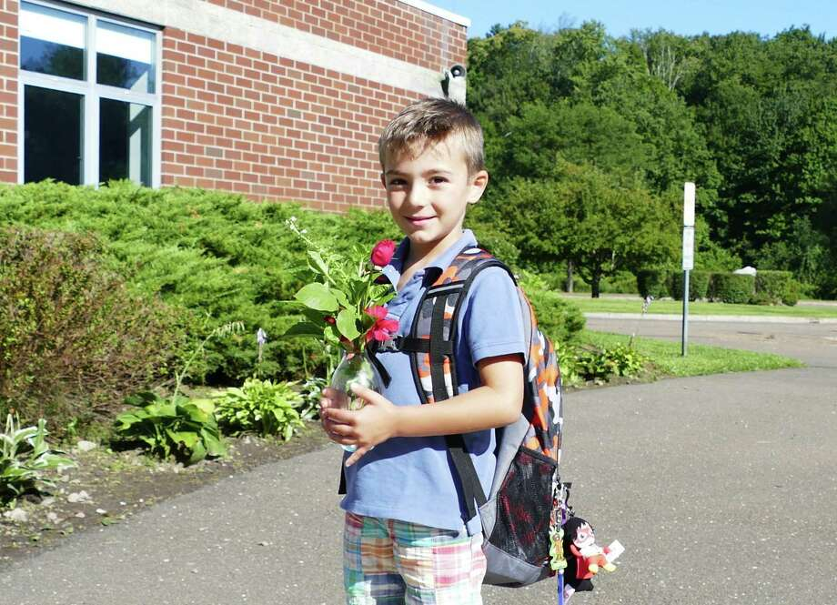 "Max Frattaroli, 5, brings roses for his teacher at the school in New Canaan on the first day of school August 29, 2019. He was excited to get back to school because ""I get to meet my class,"" he said. East School's roof is behind Frattaroli, and has been protecting the school for 25 years. Photo: Grace Duffield / Hearst Connecticut Media"