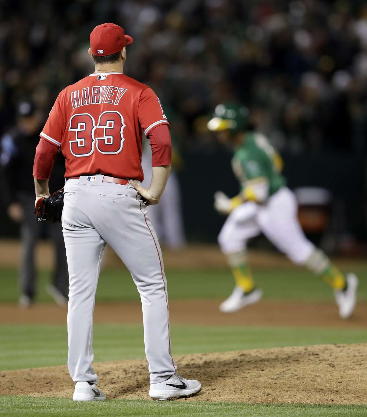 Los Angeles Angels pitcher Matt Harvey (33) waits for Oakland Athletics' Khris Davis to run the bases on a two-run home run during the sixth inning of a baseball game Friday, March 29, 2019, in Oakland, Calif.