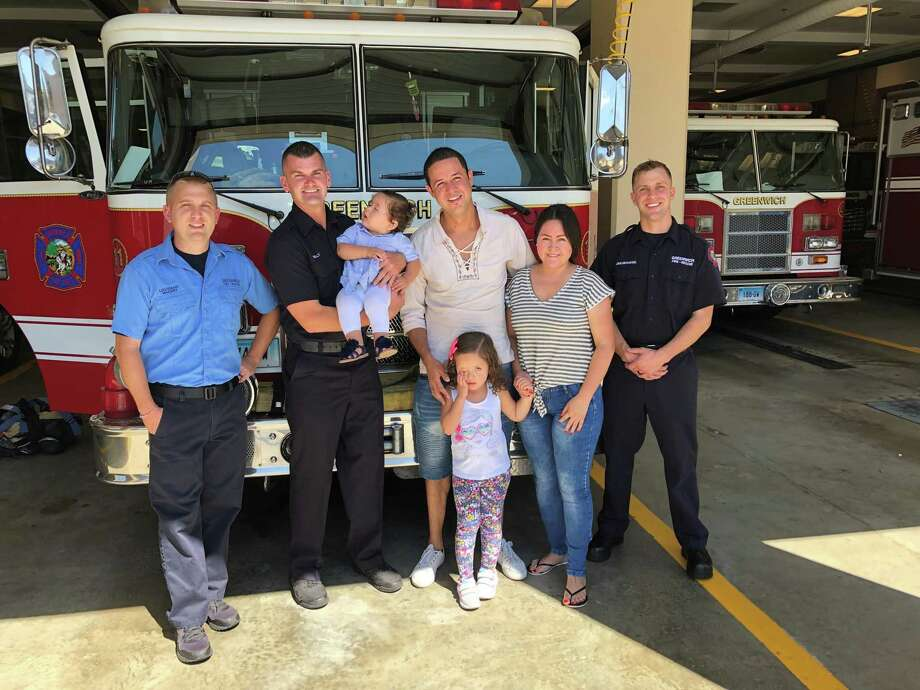 Erik Maziarz, Chris Kelly, Sophia Rincon, Juan Rincon, Luciana Rincon, aged 4, Luc Rincon and Adam Jakubowski meet at the downtown fire station Thursday. The firefighters helped revive the infant on Aug. 13, and her family came by to offer thanks. Photo: / Contributed