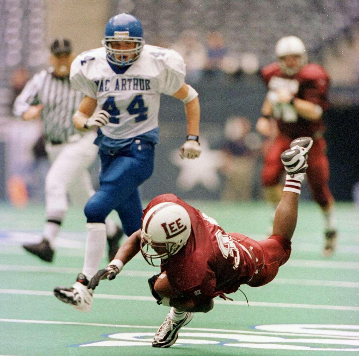 In Texas Stadium in Dallas Saturday Dec. 19, 1998, Midland Lee High School TB Cedric Benson , who scored 5 TD's (1pass) and 4 runs, stumbles in the 2nd quarter as San Antonio's MacArthur High School LB Joey Johnson (44) looks on.