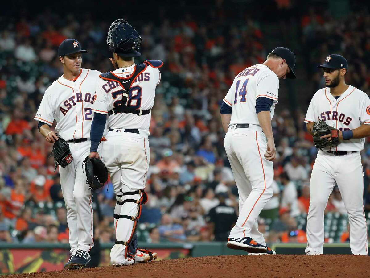 Houston Astros starting pitcher Zack Greinke (21) stops to talk to catcher Robinson Chirinos (28) after getting pulled by manager AJ Hinch (14)during the sixth inning of an MLB baseball game at Minute Maid Park, Thursday, August 29, 2019.