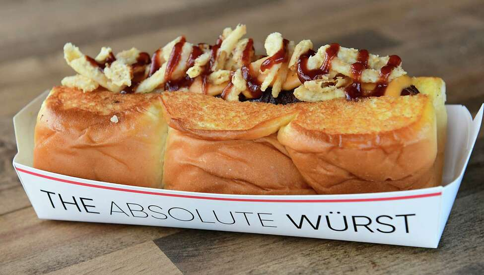 Cowboy haus dog - smoked bacon wrapped dog, cheddar cheese sauce, crispy onions, BBQ sauce at Dog Haus Biergarten.