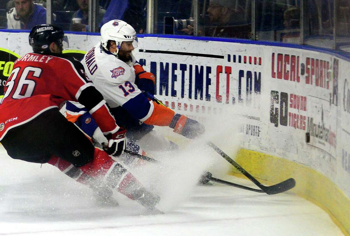 The Sound Tigers' Colin McDonald brakes in the corner as he and Portland's Brandon Gormley chase the puck during a game in 2015 at the Webster Bank in Bridgeport.