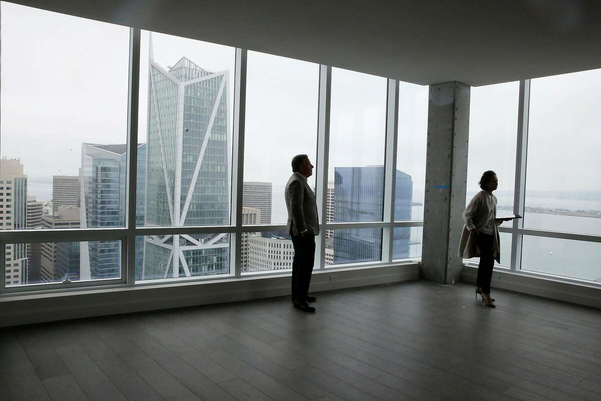 Gregg Lynn (l to r), broker with Sotheby's International Realty, and Edie Narrido, Avery sales director walk past windows looking out onto the view from a penthouse at the Avery on Monday, August 19, 2019 in San Francisco, CA.
