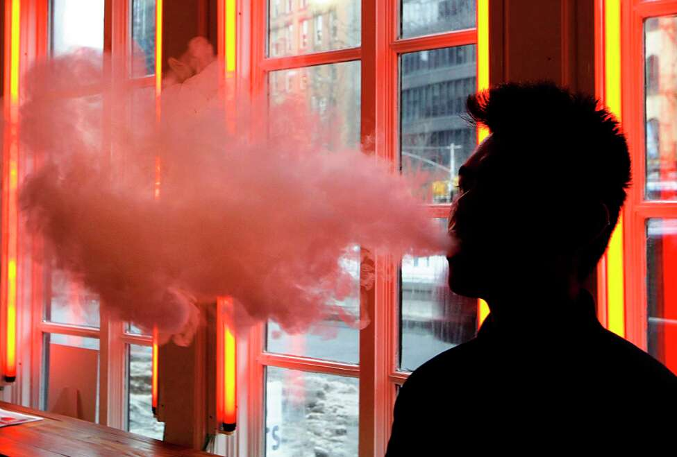 FILE - In this Feb. 20, 2014, file photo, a patron exhales vapor from an e-cigarette at a store in New York. Under the Trump administration, former FDA commissioner Scott Gottlieb kicked off his tenure in 2017 with the goal of making cigarettes less addictive by drastically cutting nicotine levels. He also rebooted the agencya€™s effort to ban menthol flavoring in cigarettes. But those efforts have been largely eclipsed by the need to respond to an unexpected explosion in e-cigarette use by teens. (AP Photo/Frank Franklin II, File)