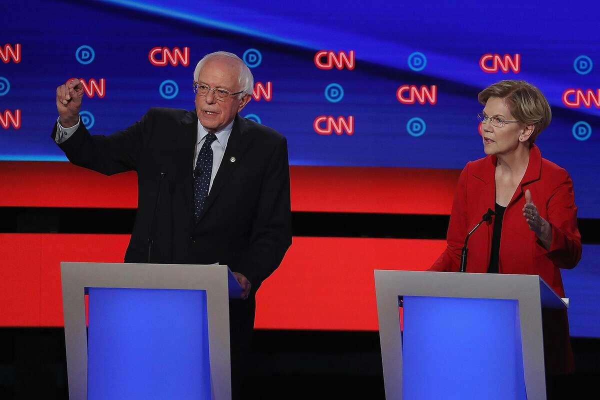 Democratic presidential candidate Sen. Bernie Sanders (I-Vt.), left, and Sen. Elizabeth Warren (D-Mass.) speak during the Democratic Presidential Debate at the Fox Theatre on Tuesday, July 30, 2019, in Detroit.