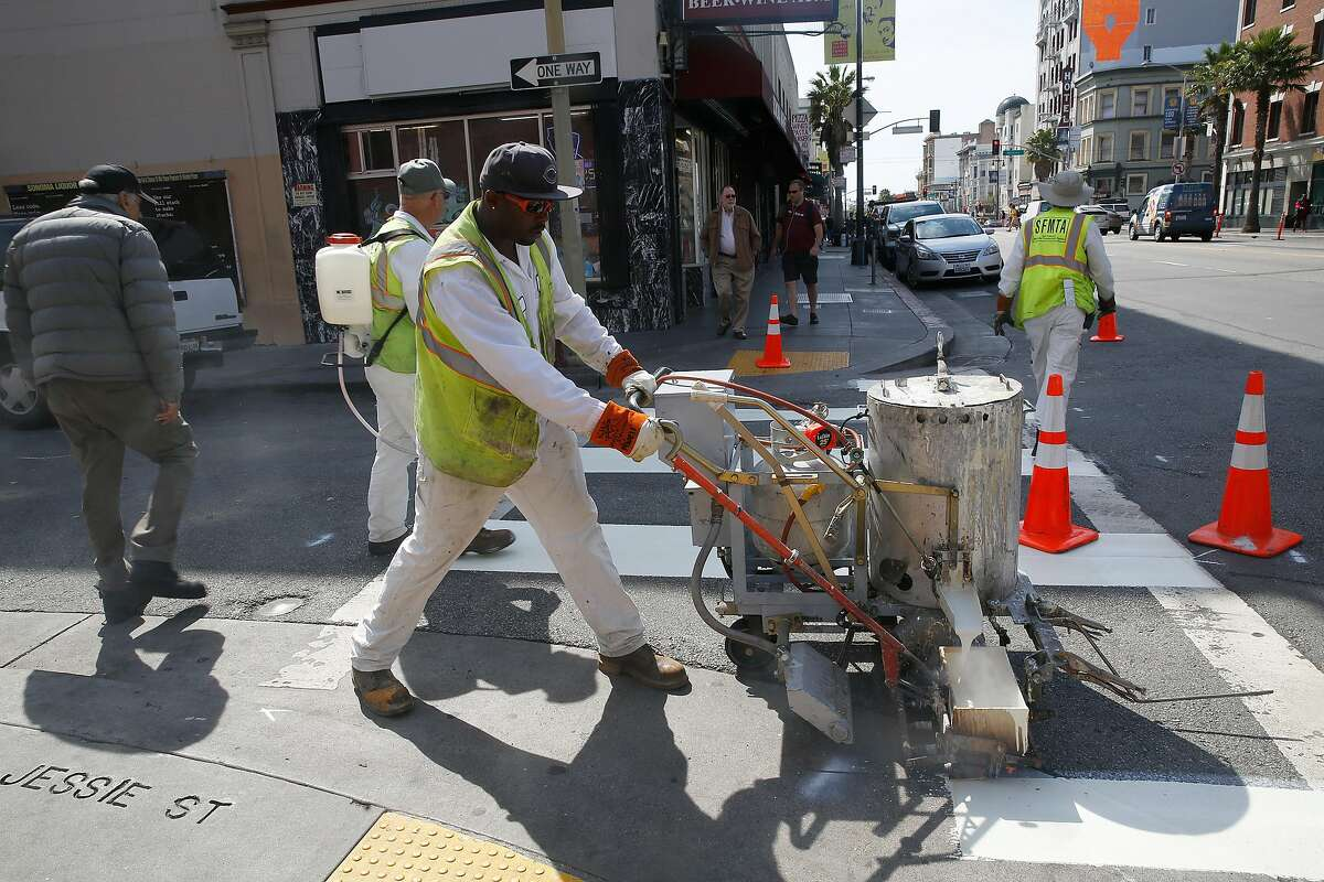 San Francisco Municipal Transportation agency employees paint more lines to pedestrian walks on 6th at Stevenson streets in San Francisco, Calif., on Wednesday, July 1, 2015. The Vision Zero plan is one of the city's projects to reduce pedestrian and bicyclists deaths to zero.