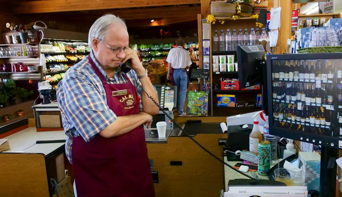 Cal Mart owner Bill Shaw helps customer on the phone, Thursday Aug. 29, 2019, in downtown Calistoga, Ca. He is prepared to rent a generator if need for a PG&E shutdown.