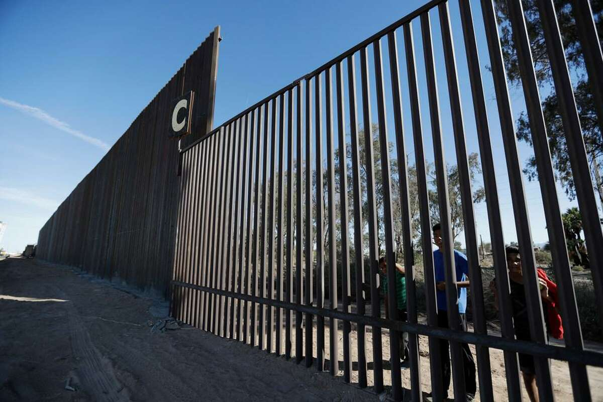 In this March 5, 2018, file photo, boys look through an older section of the border structure from Mexicali, Mexico, alongside a newly-constructed, taller section, left, in Calexico, Calif. A federal appeals court has rejected arguments by the state of California and environmental groups who tried to block reconstruction of sections of the U.S.-Mexico border wall. The 9th U.S. Circuit Court of Appeals ruled Monday, Feb. 11, 2019, that the Trump administration did not exceed its authority by waiving environmental regulations to rebuild sections of wall near San Diego and Calexico.