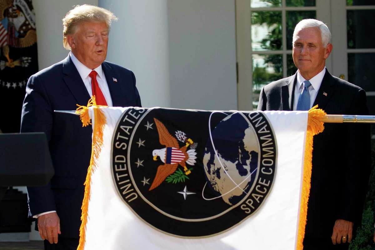 President Donald Trump, and Vice President Mike Pence, watch as the U.S. Space Command flag is unfurled during a ceremony to establish the U.S. Space Command in the Rose Garden of the White House in Washington, Thursday, Aug. 29, 2019. (AP Photo/Carolyn Kaster)