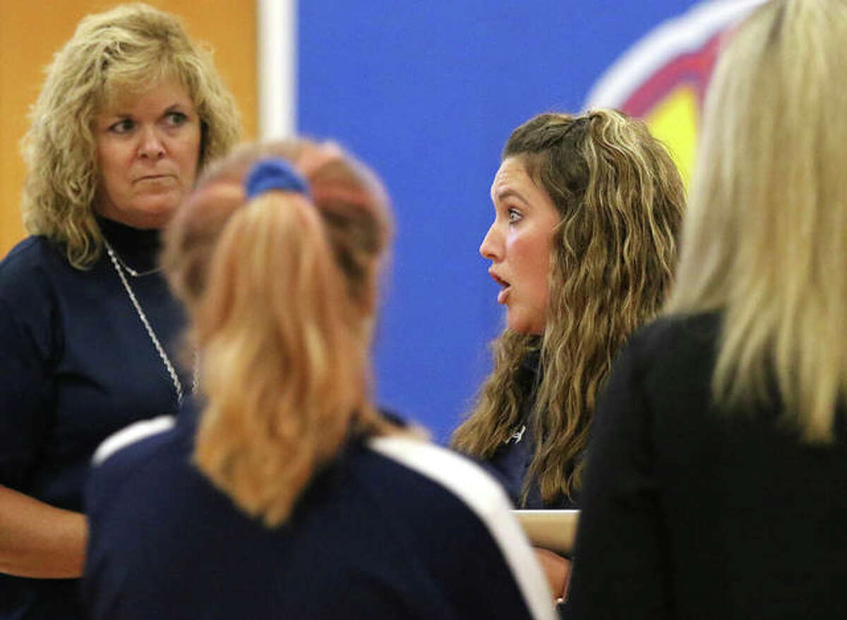 Jersey coach Toni Goetten (right) addresses her team during a timeout while assistant Sue Long (left) listens in during Monday's play at the Roxana Tourney.