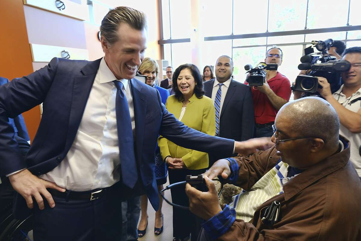 CORRECTS NAME OF PATIENT TO DETROIT FARMER, INSTEAD OF JOE DIAZ - California Governor Gavin Newsom greets patient Detroit Farmer, right, during a tour at the Rancho Los Amigos National Rehabilitation Center in Downey, Calif., on Wednesday, April 17, 2019. (AP Photo/Richard Vogel)