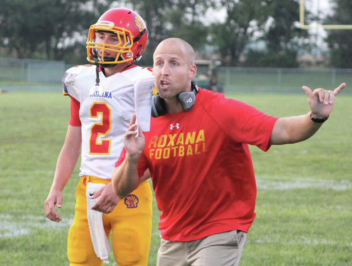Roxana coach Wade DeVries (right) tries to get an official's attention while conferring with quarterback Gavin Huffman during a game last season in Piasa.