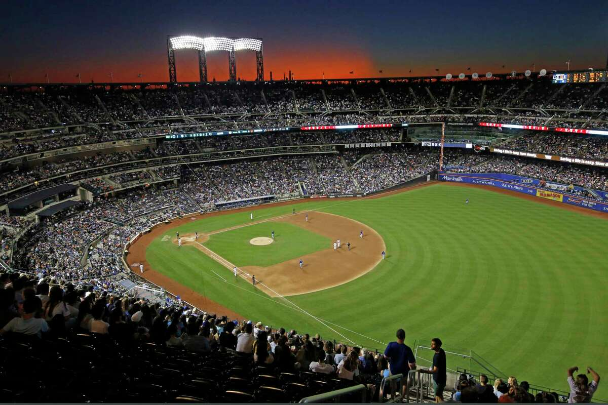 The sun sets behind CitiField during a baseball game between the New York Mets and the Chicago Cubs, Thursday, Aug. 29, 2019, in New York. (AP Photo/Kathy Willens)