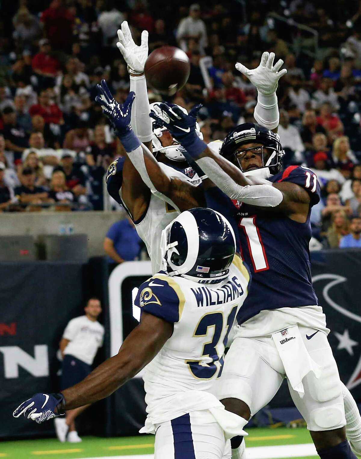 Los Angeles Rams defensive back Darious Williams (31) breaks up a pass intended for Houston Texans wide receiver Steven Mitchell (11) during an NFL preseason football game at NRG Stadium on Thursday, Aug. 29, 2019, in Houston.