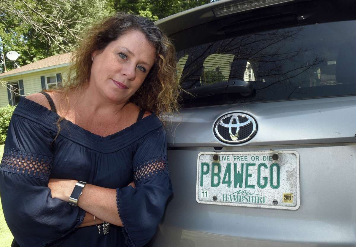 This Aug. 26, 2019 photo shows Wendy Auger standing by her vehicle in Rochester, N.H. The state Division of Motor Vehicles asked Auger to surrender the plate, which reads