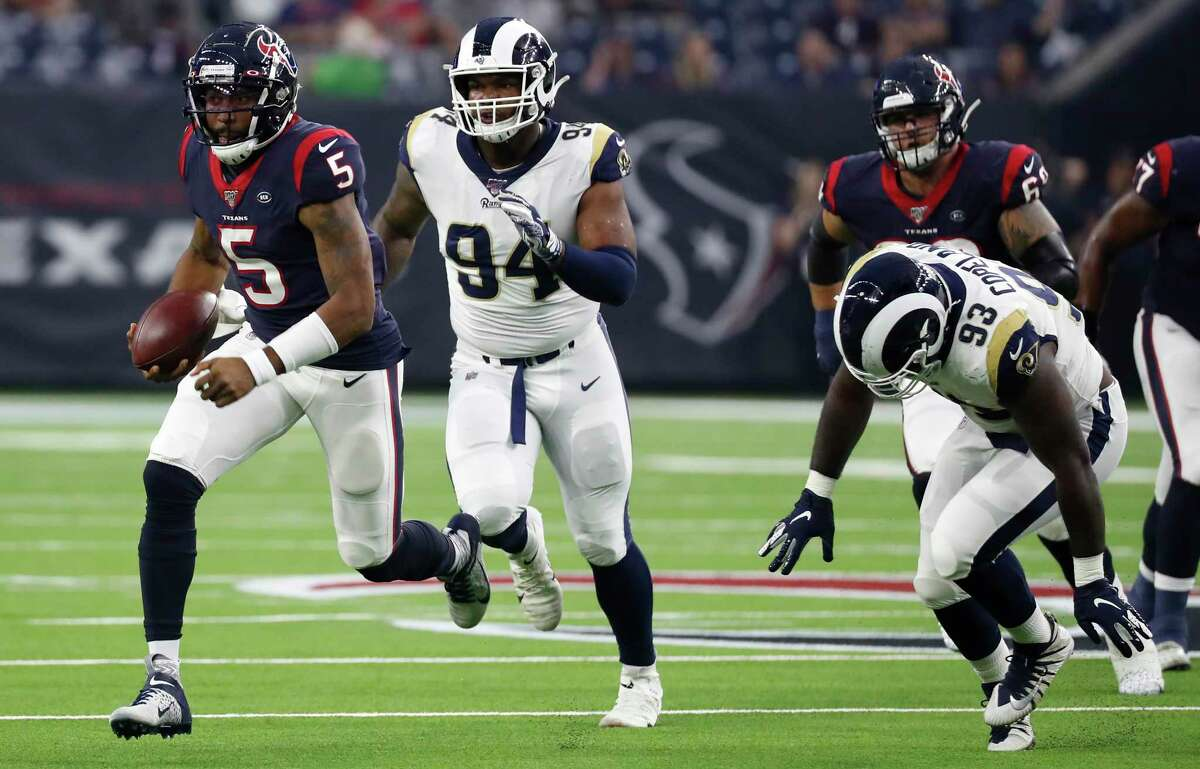 Houston Texans quarterback Joe Webb (5) is chased out of the pocket by Los Angeles Rams defensive end John Franklin-Myers (94) and defensive tackle Marquise Copeland (93) for a 33-yard run and a first down during an NFL preseason football game at NRG Stadium on Thursday, Aug. 29, 2019, in Houston.