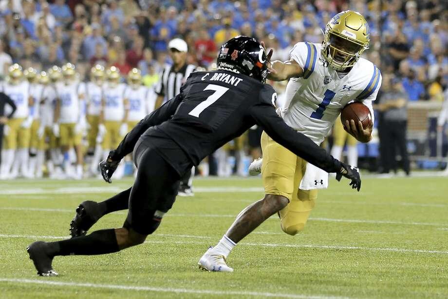 UCLA QB Dorian Thompson-Robinson tries to elude Cincinnati cornerback Coby Bryant. Photo: Kareem Elgazzar / Associated Press