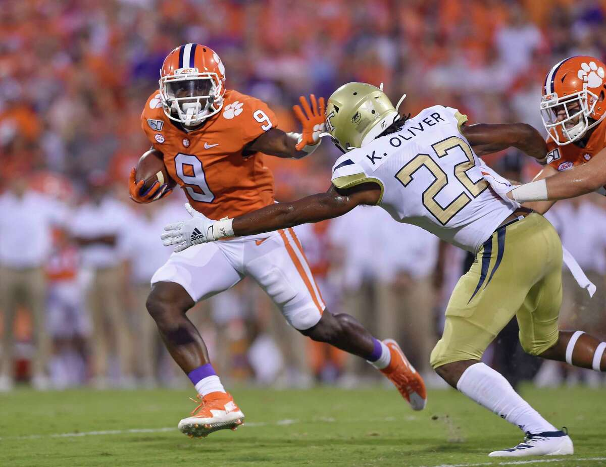 Clemson's Travis Etienne (9) fends off Georgia Tech's Kaleb Oliver to gain a first down during the first half of an NCAA college football game Thursday, Aug. 29, 2019, in Clemson, S.C. (AP Photo/Richard Shiro)