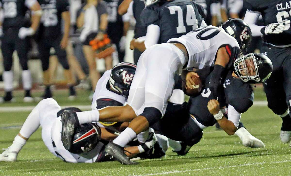 Clark quaterback David Santos is sacked by Churchill Linebacker Eric Munoz along with other teammates in second half action. Churchill defeated Clark 19-0 on Thursday, August 30, 2019 at Farris Stadium.