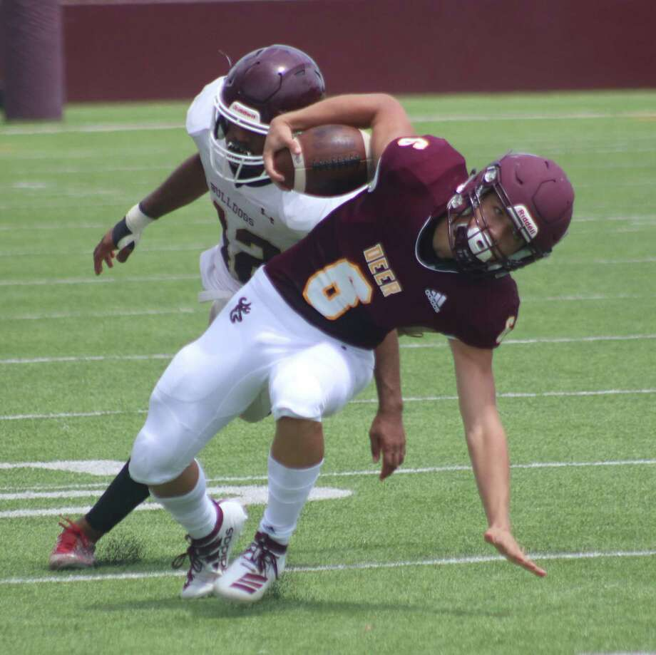 Deer Park's Alex Argueta stays on his feet after catching a pass and avoiding a defender during the scrimmage with Summer Creek last weekend. Argueta used the reception to score one of the team's two touchdowns. Photo: Robert Avery