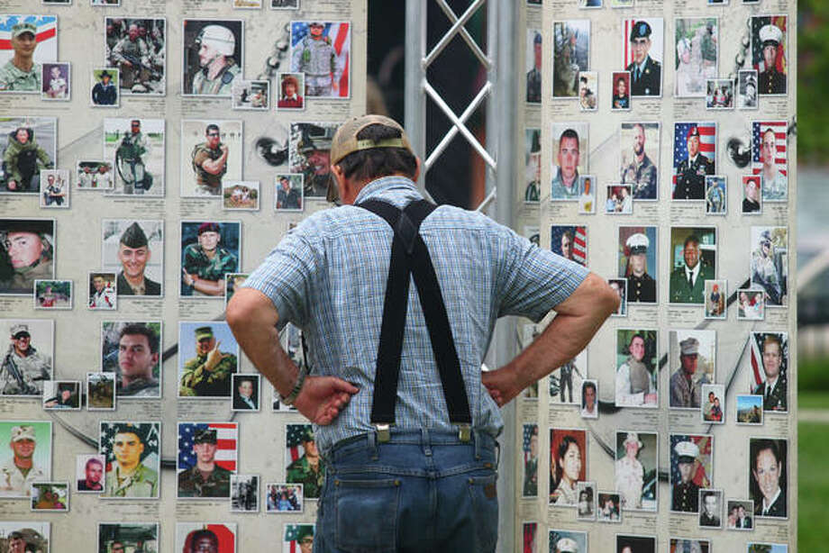 Visitors to the traveling Remembering Our Fallen memorial look at photos of the men and women of the armed services who have died since Sept. 11, 2001. Photo: Rosalind Essig | Journal-Courier