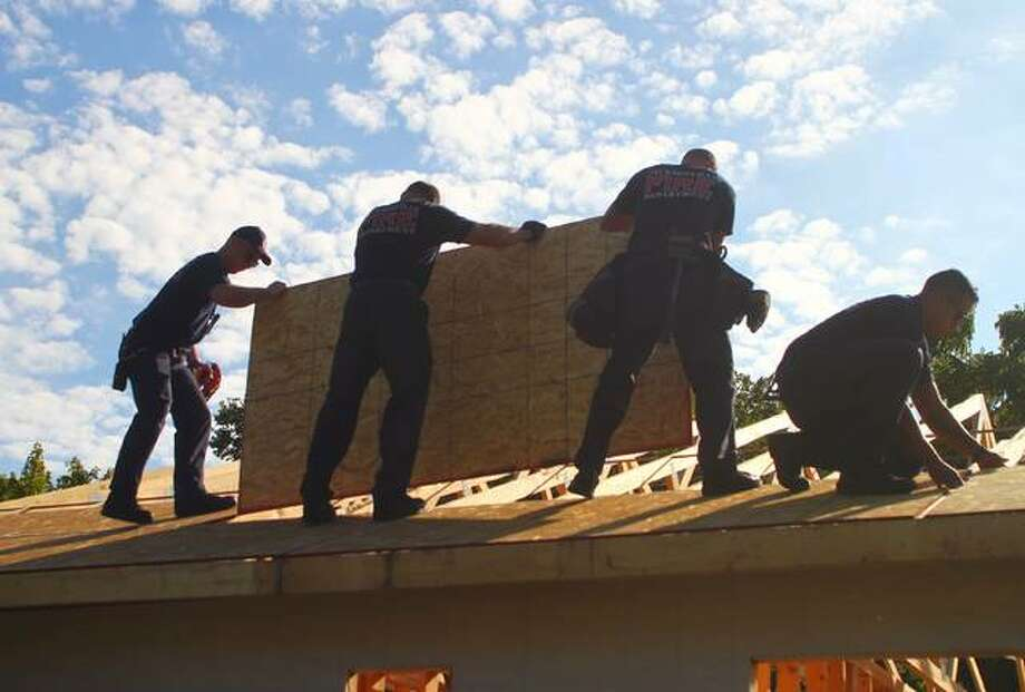 Members of the Jacksonville Fire Department lay sheeting Thursday for the roof of a Habitat for Humanity house. Photo: Samantha McDaniel-Ogletree | Journal-Courier
