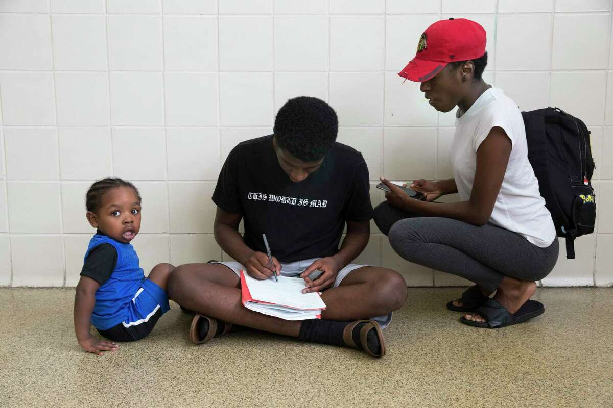 Juevon Green Jr., center, fills out the form to get his first license while his girlfriend, Devia Sorrell, and nephew, Jabar Simmonds Jr., watch in waiting area of a Texas Department of Public Safety Driver License Mega Center at South Gessner Road on Friday, Aug. 23, 2019, in Houston.