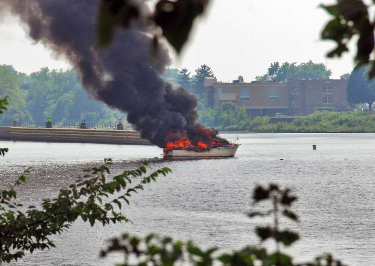 An unmanned cabin cruiser burns out of control on the Hudson River in Troy Wednesday, Aug. 4, 2010. (John Carl D'Annibale / Times Union)