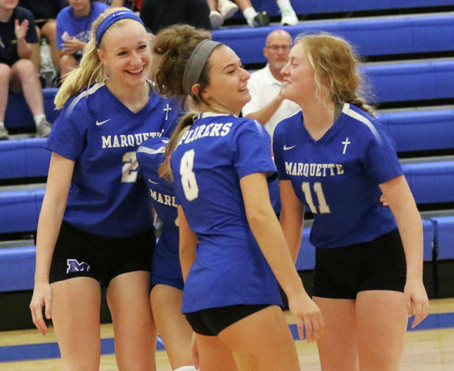 Marquette Catholic's Emma Menke (left), Ellie Jacobs (8) and Rachel Heinz (11) celebrate a point during the Roxana Tourney on Tuesday. The Explorers opened at home on Thursday with a victory over Carrollton. Photo: Greg Shashack / The Telegraph
