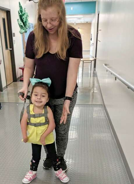 Van Raub Elementary School teacher's aid Heidi Faseler helps 4-year-old Rilyn Gonzalez as she takes her first steps on Thursday. Rilyn, who is in the school Pre-K program, was born with a condition that prevented her joints from forming properly. Photo: Boerne ISD