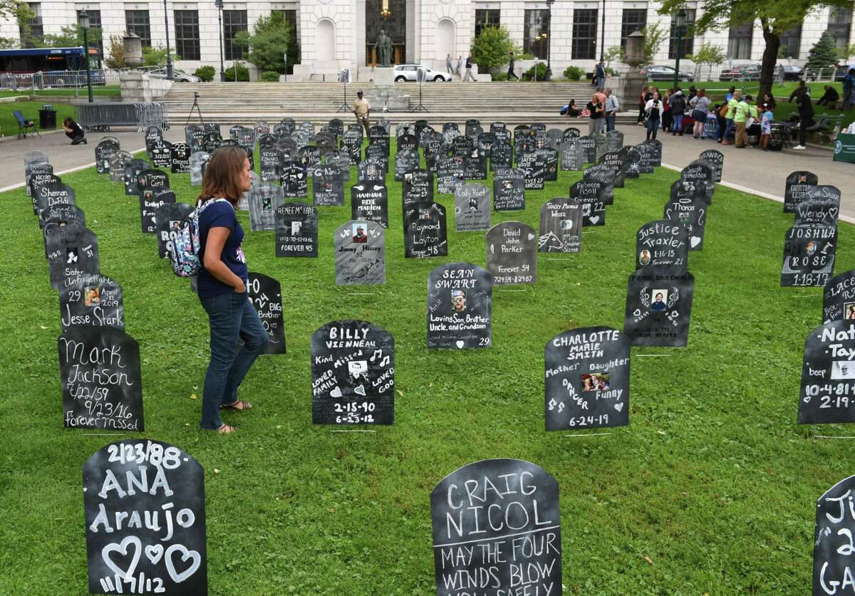 Shauna Sitts of Broadalbin, who lost her brother Bryan Sheckton to an overdose in 2014, walks through a field of gravestones representing some of the state's population lost to overdose on Friday, Aug. 30, 2019, during Capital Region Overdose Awareness Day at events at West Capitol Park in Albany, N.Y. (Will Waldron/Times Union)