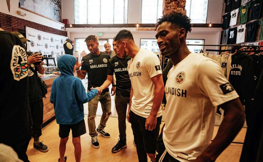 Oakland Roots players (left to right) Benji Joya, Devante Dubose, Julio Cervantes, and Yohannes Harrish talk with a young fan at the Roots jersey unveiling at  Oaklandish's downtown Oakland store on June 28,  2019. Photo: Courtesy Oakland Roots SC