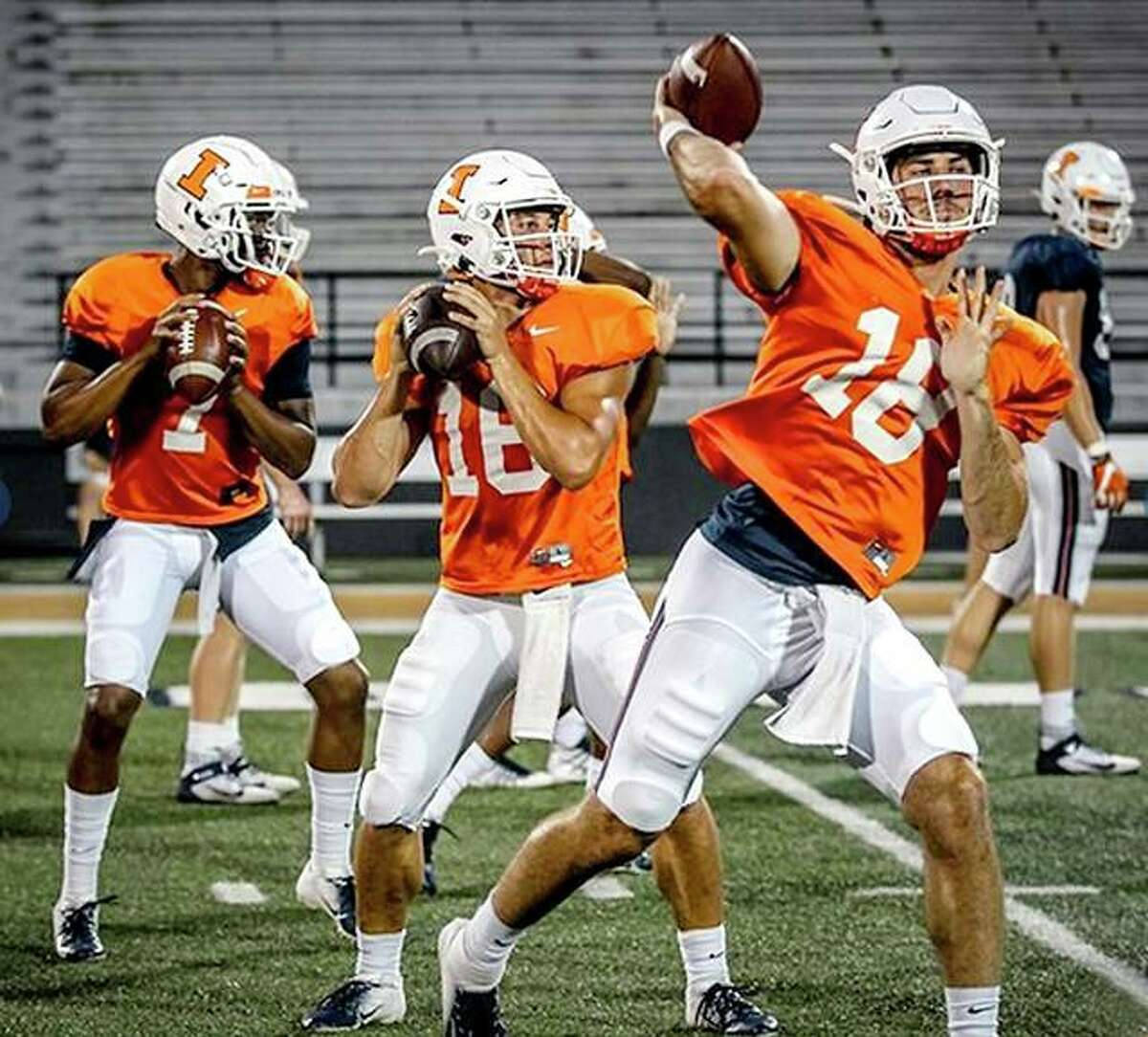 Illinois quarterback Brandon Peters (18) delivers a pass during a practice session at Memorial Stadium. Peters, a graduate transfer from Michigan, will start Saturday against Akron in the season opener. Also pictured are quarterbacks Cam Miller, center, and Isaiah Williams.