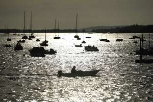 """A man rides a dinghy back to shore after anchoring his sailboat in the harbor off the coast of the island of North Haven, Maine on Tuesday, Aug. 27, 2019. Connecticut Governor Ned Lamont's great-grandfather Thomas W. Lamont, a J.P. Morgan financier, bought 100 acres on the island in 1917 and built the family estate """"Sky Farm"""" shortly thereafter. The island of North Haven is accessible by a thrice-a-day ferry from nearby Rockland and is largely seasonal with just about 350 year-round residents and more than 1,500 in the summer."""