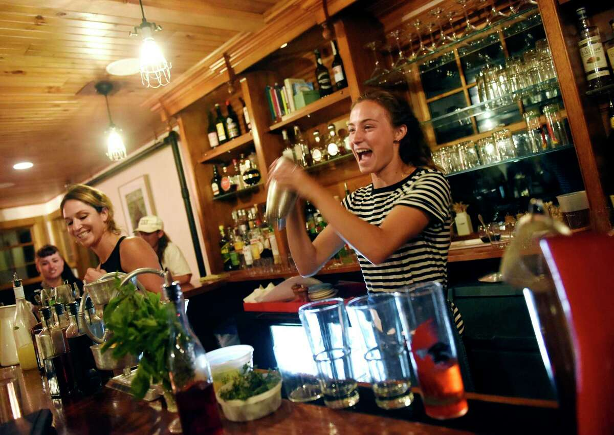 Maret Smith-Miller, a summer employee from New York City, mixes a drink at the bar at the Nebo Lodge on the island of North Haven, Maine on Tuesday, Aug. 27, 2019. Bars, nightclubs Bars and nightclubs remain closed. Source: Office of Gov. Ned Lamont