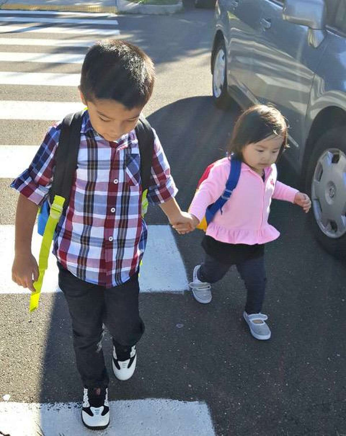 Two IRIS students are prepared for school with their backpacks.