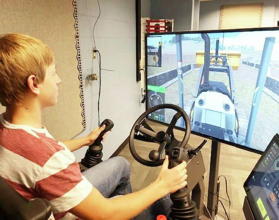 Bad Axe senior Jack Fisher operates a John Deer backhoe simulator at the Huron Area Tech Center lab.  (Courtesy Photo)