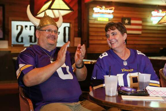 Robert Fisk, left, a diehard Vikings fan originally from Minnesota, and his wife Carrol, a newly converted fan, watch a Minnesota Vikings preseason game with other fans at Rod Dog's Saloon.