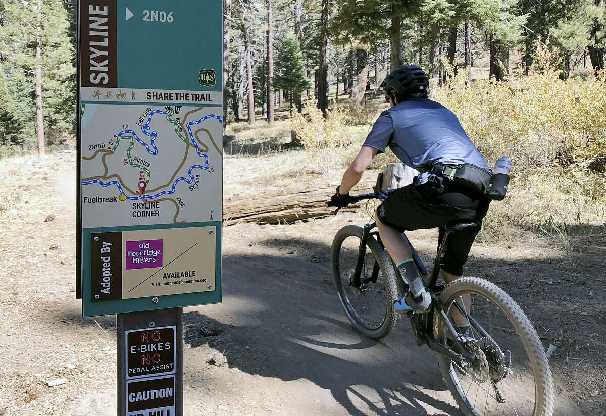 In this photo taken Sept. 23, 2018, a mountain biker pedals past a No E-bikes sign in the San Bernardino National Forest near Big Bear Lake, Calif. Motorized electric bicycles may soon be humming their way into serene national parks and other public lands nationwide. A new Trump administration order would allow so-called e-bikes on every federal trail where a regular bike can go.(AP Photo/Brian Melley)