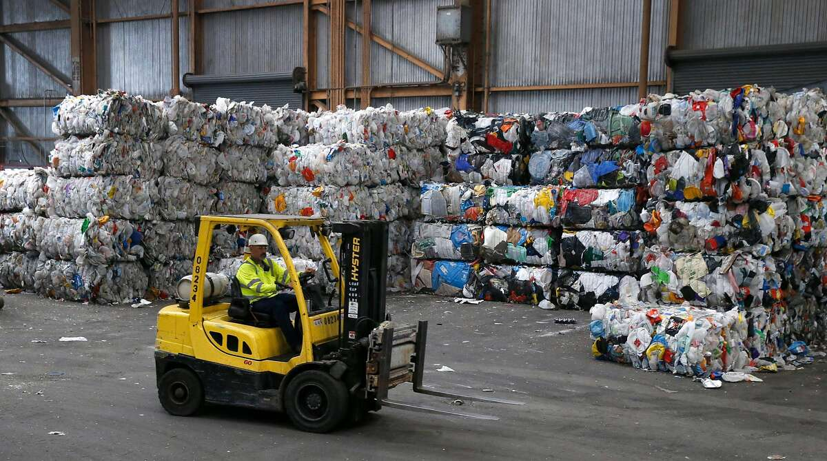 Large bales of plastic bottles and containers are stacked and await transfer away from the Recology recycling facility in San Francisco, Calif. on Thursday, Aug. 22, 2019.