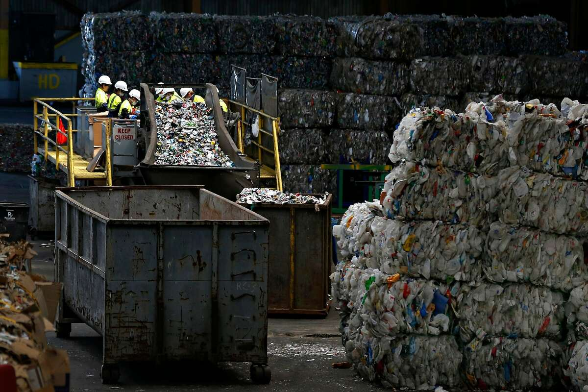 A team of workers sort aluminum cans near large bales of plastic bottles and containers (right) ready for shipping away from the Recology recycling facility in San Francisco, Calif. on Thursday, Aug. 22, 2019.