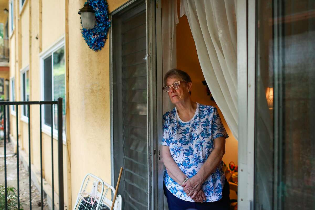 Linda Owens stands for a portrait on the porch of her apartment in Hayward, California, on Tuesday, Aug. 20, 2019. Linda, who is a foster mother, is facing a massive rent increase after her apartment complex was bought out by a real estate developer that is converting it into affordable housing.