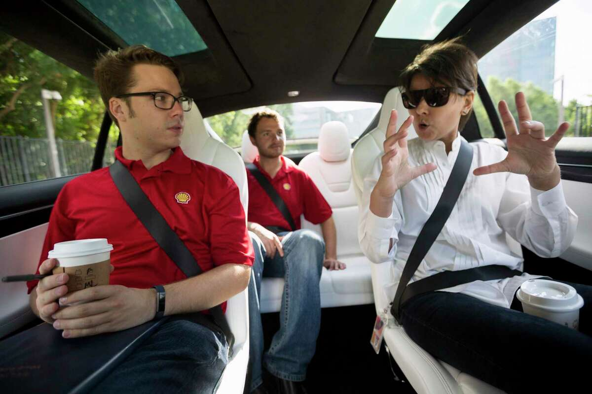From left, Shell workers Adam Harrison, Dakota Stormer and Natasha Qamar take a demo ride in an ElecTrip vehicle.