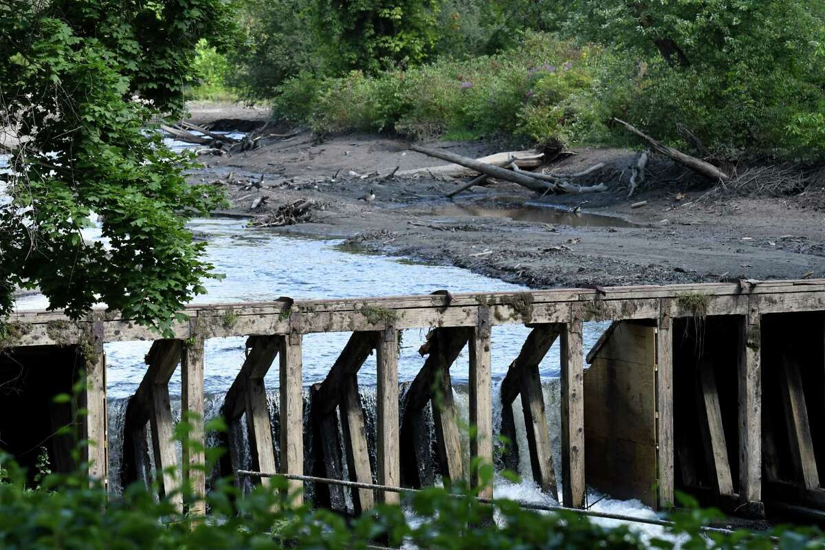 A hole is knocked through the dam creating Lake Ida on Friday, Aug. 30, 2019, in Troy, N.Y. The city is demolishing the dam. (Will Waldron/Times Union)