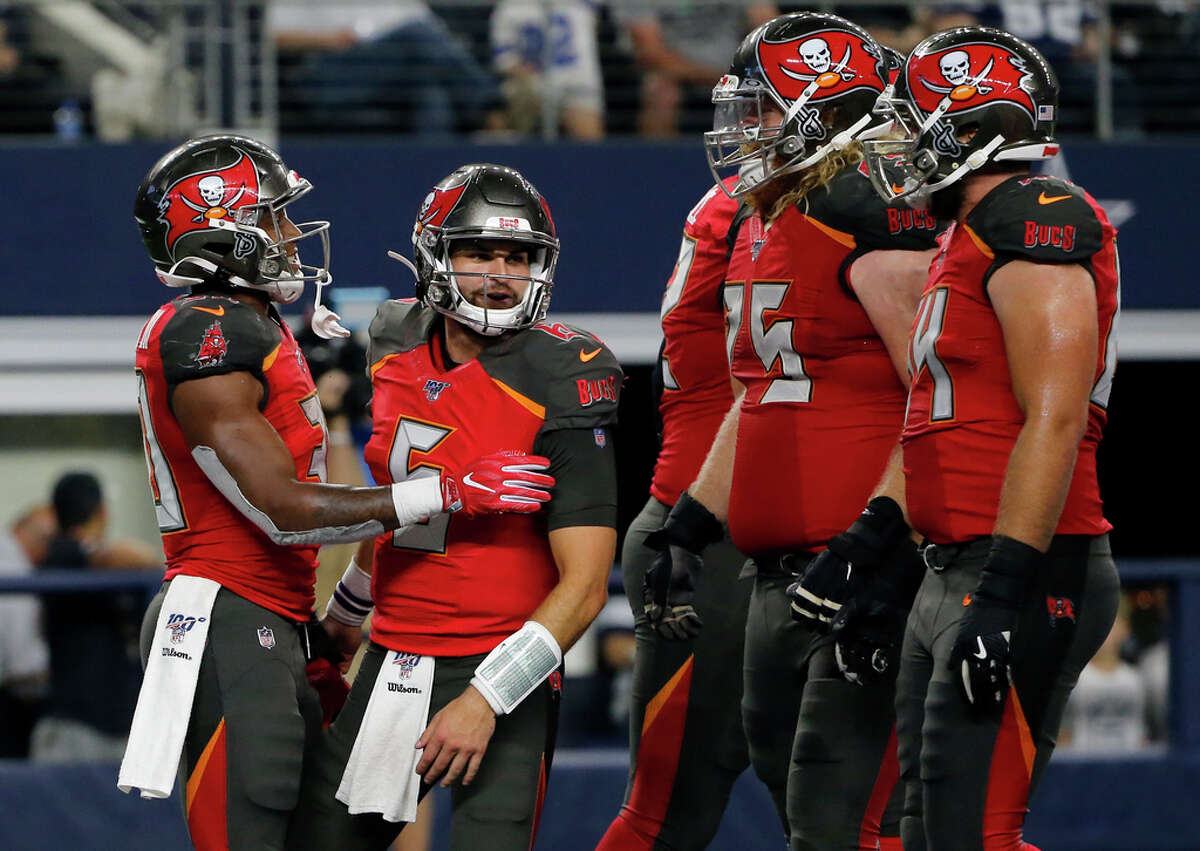 CORRECTS PLAYER NEXT TO ANDERSON TO VINCENT TESTAVERDE, INSTEAD OF CAIRO SANTOS - Tampa Bay Buccaneers running back Bruce Anderson III, left, is congratulated by quarterback Vincent Testaverde (6) and others after carrying the ball for a touchdown during the second half of the team's preseason NFL football game against the Dallas Cowboys in Arlington, Texas, Thursday, Aug. 29, 2019.