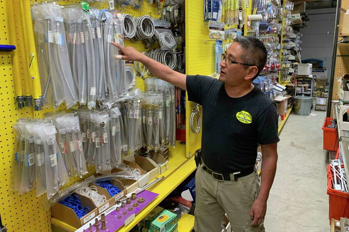 In this photo taken Wednesday, Aug. 28, 2019, Albert Chow, owner of Great Wall Hardware in San Francisco, points to steel faucet parts, whose prices have increased because of US tariffs on Chinese imports. He had to raise the price from $5.49 to $5.99. (AP Photo/Terry Chea)