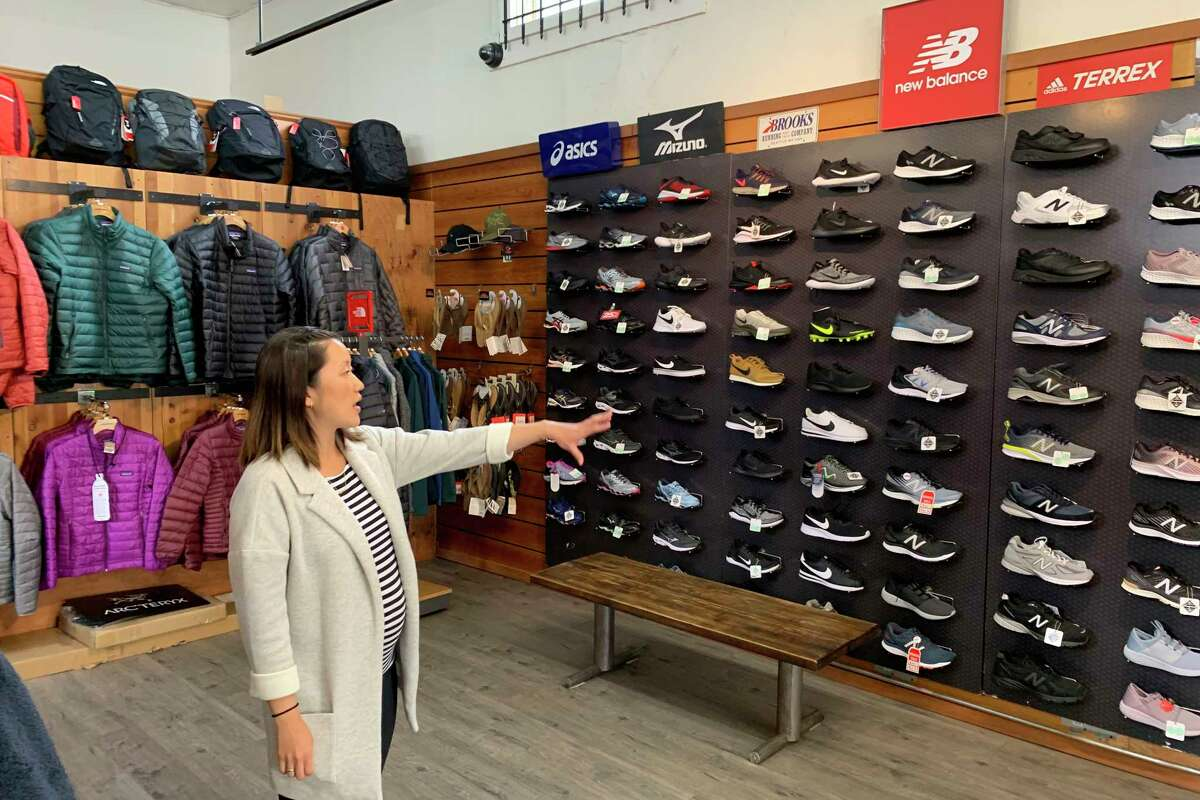 In this photo taken Wednesday, Aug. 28, 2019, Jennifer Lee, whose family owns Footprint shoe story in San Francisco, points to wall of athletic shoes, many of which are made in China and will be subject to new US tariffs on Chinese goods starting Sept 1. (AP Photo/Terry Chea)
